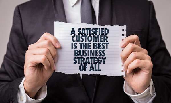 Person holding a torn note saying A satisfied customer is the best business stratgey of all