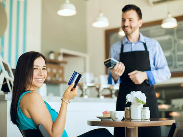 Person paying by card in a cafe